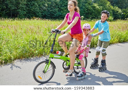 Mother and children ride bicycle and rollers on sunny day in park - stock photo