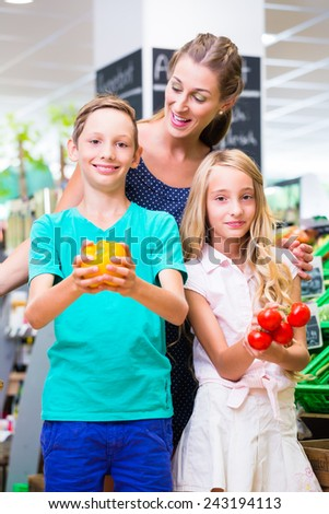 Mother and children selecting vegetables while grocery shopping in organic supermarket  - stock photo
