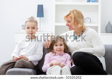 Mother and children sitting together on couch at living room. - stock photo