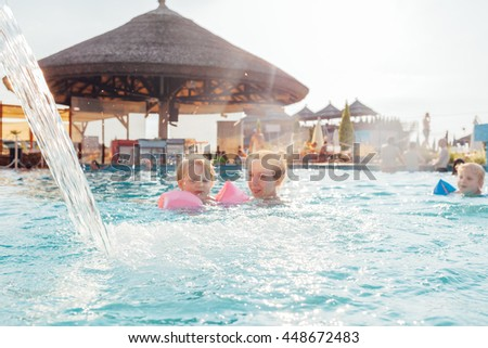 Mother and children swimming in the pool under waterfall - stock photo