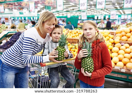 Mother and children with pineapples in fruit department in the supermarket - stock photo