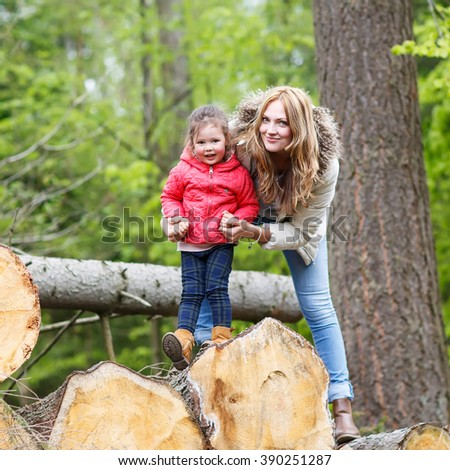 Mother and cute kid girl outdoors playing, kissing and hugging. Happy family of two, young smiling woman and her cute toddler daughter enjoying beautiful day in the forest - stock photo