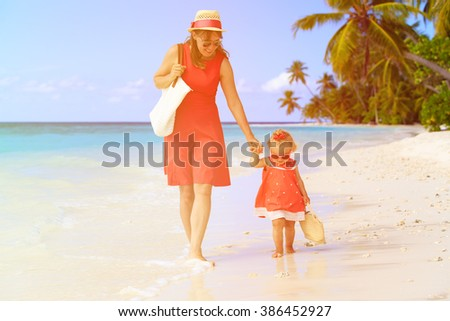 mother and cute little daughter walking on beach - stock photo