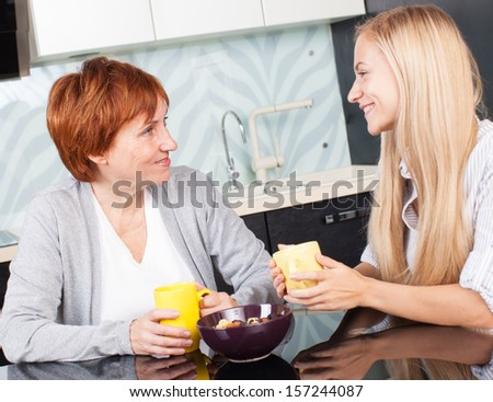 Mother and daudhter talking on the kitchen. Women at home - stock photo