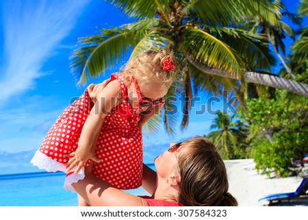 mother and daugher playing on summer tropical beach - stock photo