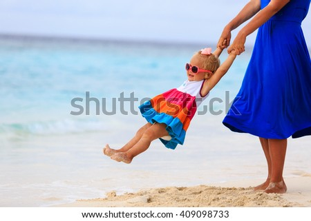 mother and daugher playing on tropical beach - stock photo