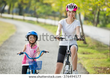 Mother and daughter are biking to the park - stock photo
