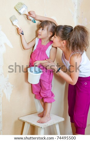 Mother and daughter are doing repairs together, primed the wall under the wallpaper - stock photo