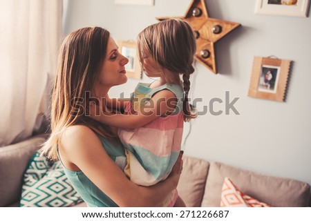mother and daughter are happy playing together at home - stock photo