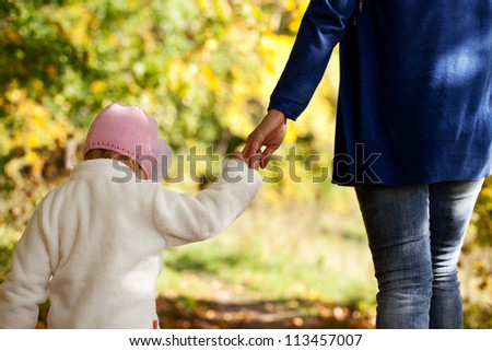 Mother and daughter are holding hands in the autumn forest - stock photo