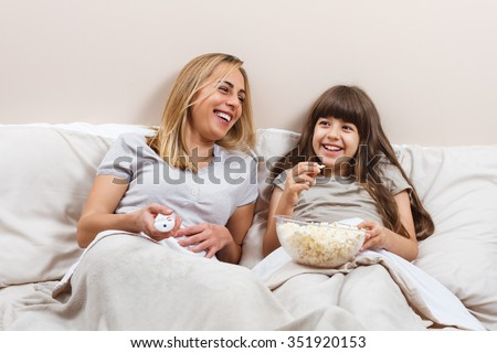 Mother and daughter are sitting on bed in pajamas and watching tv together.Family time  - stock photo