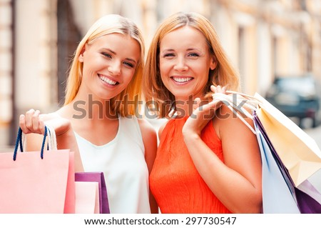 Mother and daughter are the best friends. Beautiful mature woman and her blond hair daughter holding shopping bags and looking at camera while standing outdoors - stock photo