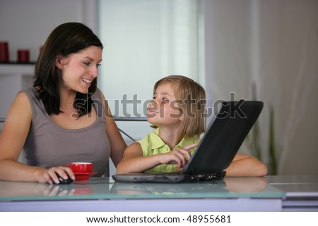 Mother and daughter at home with laptop - stock photo