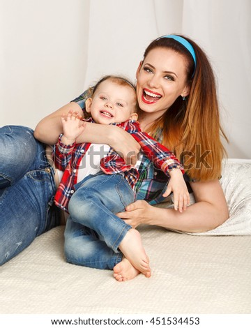Mother and daughter at home. Young mother and baby daughter hugging. Girls dressed in plaid shirt. Daughter barefoot. Laughter and smiles. Family time - stock photo