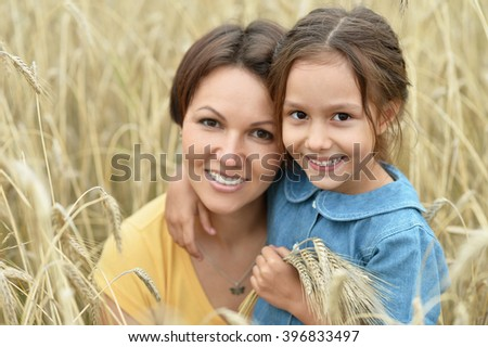 mother and daughter at  wheat field - stock photo