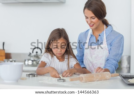 Mother and daughter baking together in the kitchen - stock photo