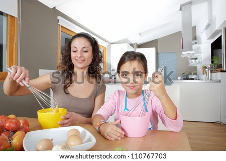Mother and daughter beating eggs in the kitchen at home while sitting together at a wooden table. - stock photo