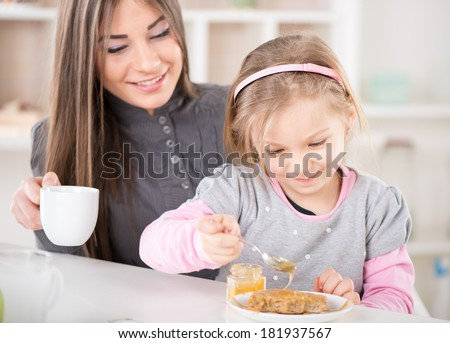 Mother and daughter breakfast in the kitchen. Cute little girl smear honey over the peanut butter on bread. Mother drinking coffee. - stock photo