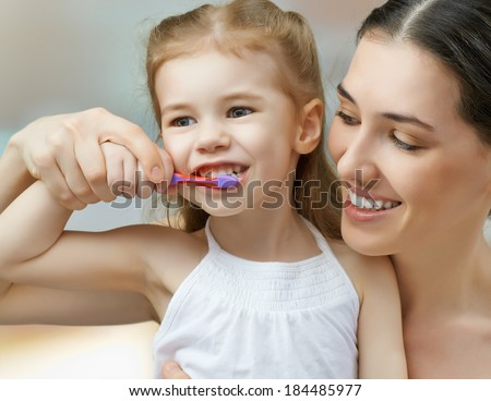 mother and daughter brush my teeth - stock photo