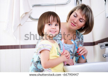 Mother and daughter brushing their teeth in bathroom - stock photo