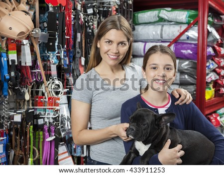 Mother And Daughter Carrying French Bulldog In Store - stock photo