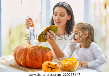 Mother and daughter carving pumpkin - stock photo