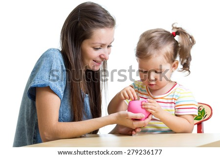 Mother and daughter child putting coins into piggy bank - stock photo