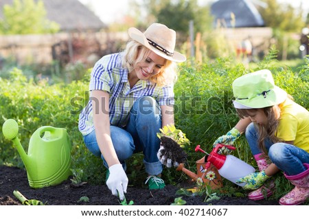 Mother and Daughter Child Watering Plants in Garden. - stock photo