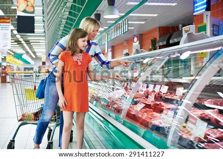 Mother and daughter chooses a meat in the supermarket - stock photo