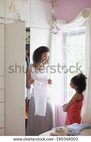 Mother and daughter choosing dress - stock photo