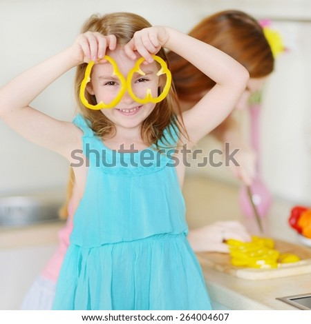 Mother and daughter cooking dinner in a kitchen - stock photo