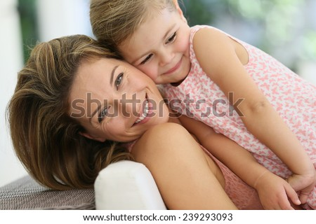 Mother and daughter cuddling at home - stock photo