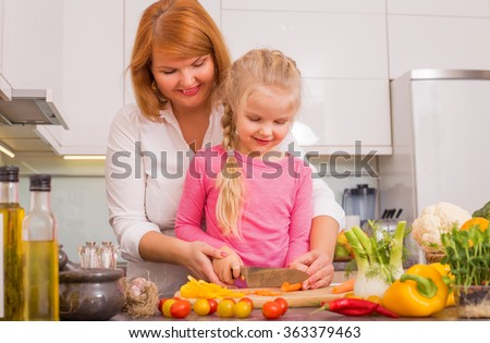 Mother and daughter cutting vegetables in kitchen  - stock photo