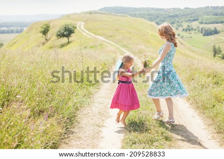 Mother and daughter dancing in sunlight on the meadow - stock photo