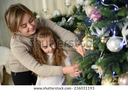 Mother and daughter decorate a Christmas tree. Family holiday - stock photo