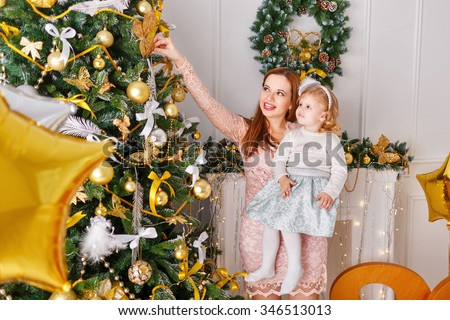 Mother and daughter decorate a Christmas tree. Mother keeps child in her arms. Holiday and fun. 2017 - stock photo