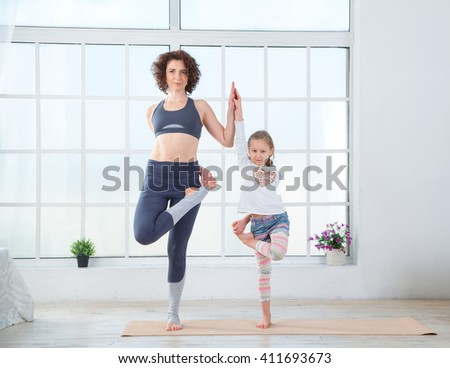 Mother and daughter do gymnastics exercises. Fitness adult woman with her child. Morning exercises, yoga - do at home all together. Grandmother and granddaughter doing yoga exercise home. - stock photo