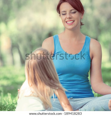 Mother and daughter doing exercise outdoors - mother teaching her daughter how to do exercises. Retro filter photo - stock photo
