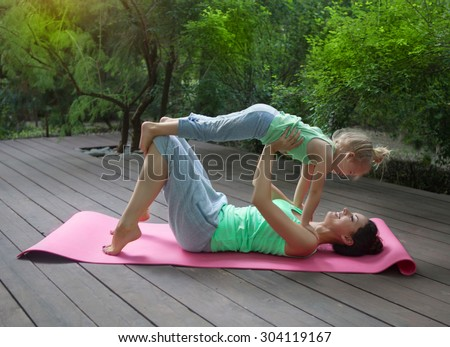 Mother and daughter doing exercise practicing yoga outdoors. Healthy lifestyle - stock photo