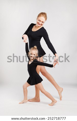 Mother and daughter doing gymnastics - mother teaching her daughter how to do exercises - stock photo