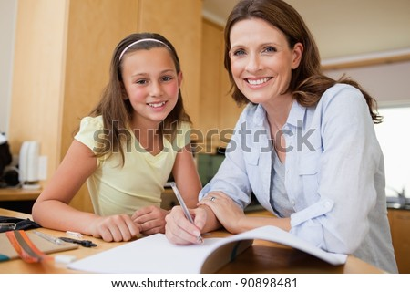 Mother and daughter doing homework together - stock photo