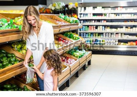 Mother and daughter doing shopping in grocery store - stock photo