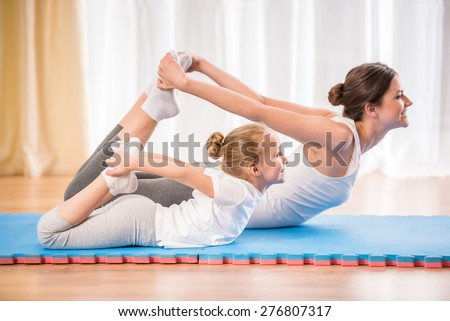 Mother and daughter doing yoga exercises on rug at home. - stock photo