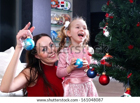 mother and daughter dress up a Christmas tree - stock photo