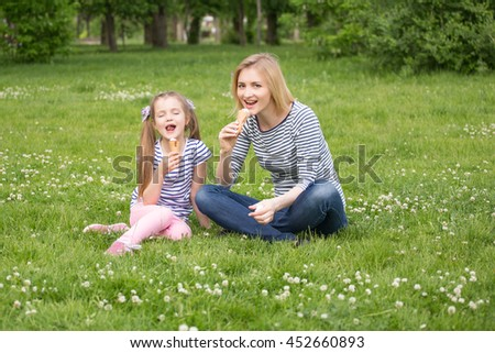 Mother and daughter eating ice-cream in the park - stock photo