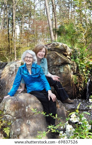 Mother and daughter enjoy springtime surrounded by foliage, trees and a trickling waterfall.  Both are smiling and sitting close together. - stock photo