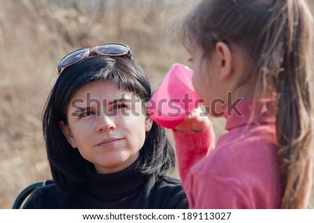 Mother and daughter enjoying a healthy picnic - stock photo