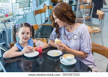 Mother and daughter enjoying cakes in coffee shop - stock photo