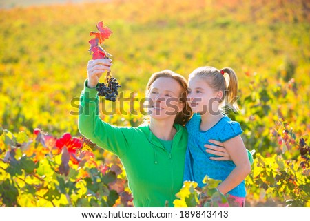 Mother and daughter family on autumn vineyard happy smiling holding grape bunch - stock photo