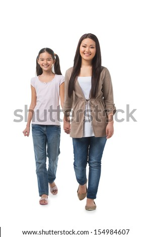 Mother and daughter. Full length of cheerful mother and daughter walking together while isolated on white - stock photo
